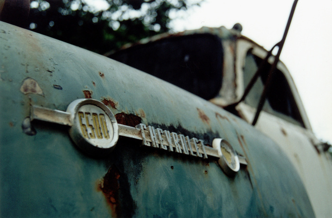 rusted chevrolet brand logo on old truck